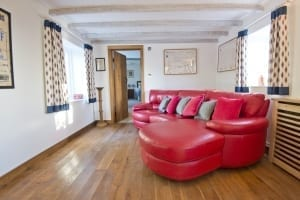small living room with red leather sofa
